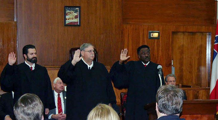 Three judges with arms raised during swearing