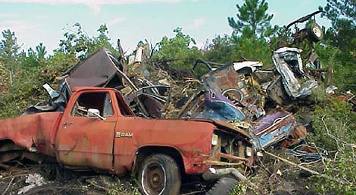 Image of decrepit truck and garbage in woods